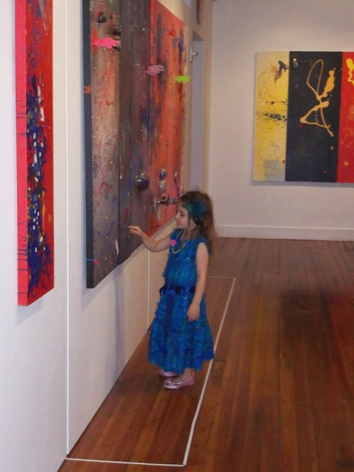 Aelita Andre Pointing to Paintings